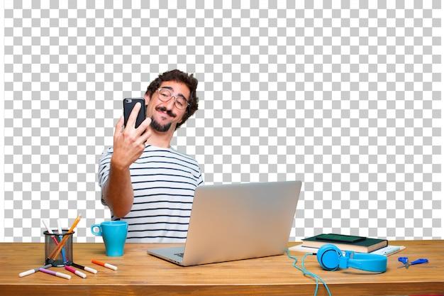Jonge gekke grafische ontwerper op een bureau met laptop en met een slimme telefoon van het aanrakingsscherm
