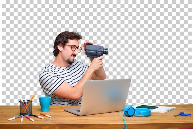Jonge gekke grafische ontwerper op een bureau met laptop en met een uitstekende bioskoopcamera