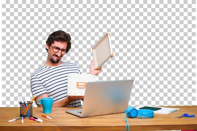Jonge gekke grafische ontwerper op een bureau met laptop en met een uitstekende doos