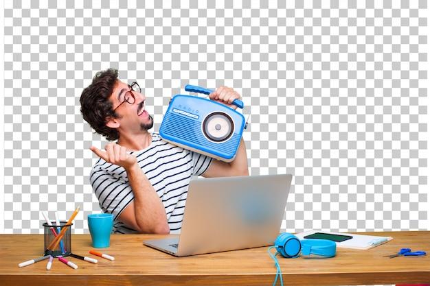 Jonge gekke grafische ontwerper op een bureau met laptop en met een uitstekende radio