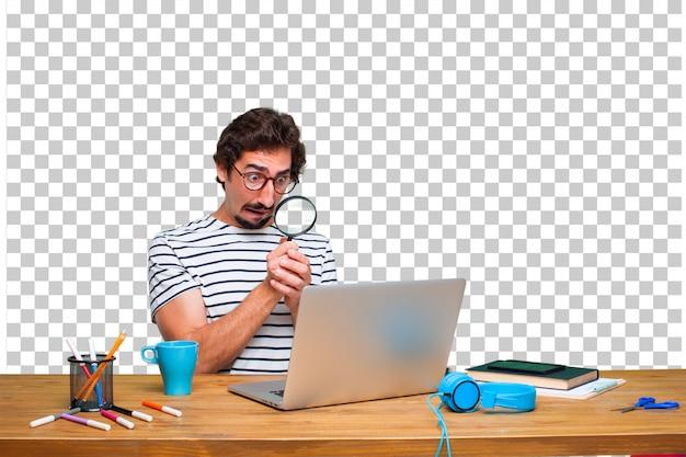 Jonge gekke grafische ontwerper op een bureau met laptop en met een vergrootglas