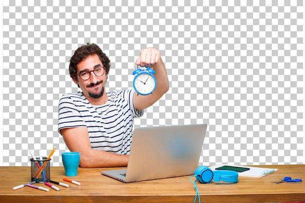 Jonge gekke grafische ontwerper op een bureau met laptop en met een wekker