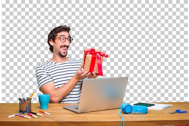 Jonge gekke grafische ontwerper op een bureau met laptop en met het concept van de giftdoos