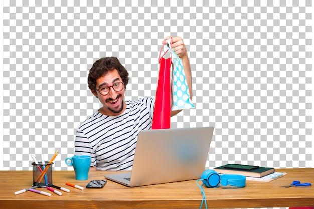 Jonge gekke grafische ontwerper op een bureau met laptop en met het winkelen zakken