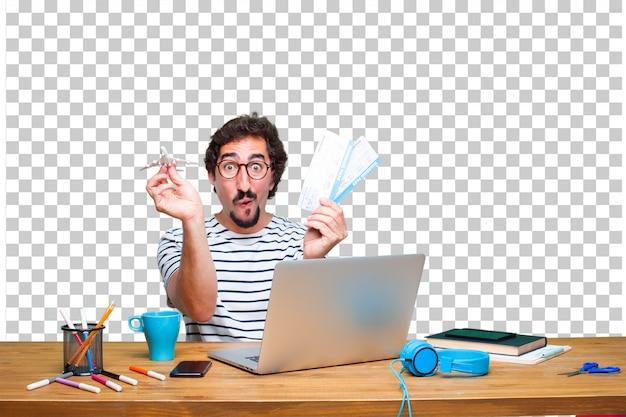 Jonge gekke grafische ontwerper op een bureau met laptop en