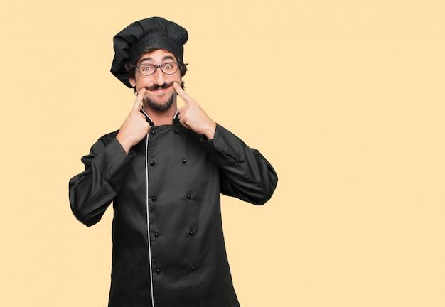 Jonge gekke man als kok dwingt een glimlach op zijn gezicht