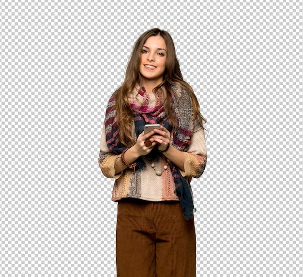 Jonge hippievrouw die een bericht met mobiel verzenden
