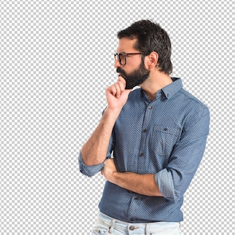Jonge hipstermens die over witte achtergrond denkt
