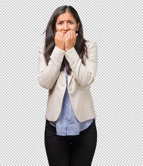 Jonge indiase vrouw die nagels bijt, nerveus en erg angstig en bang voor de toekomst, voelt paniek en stress