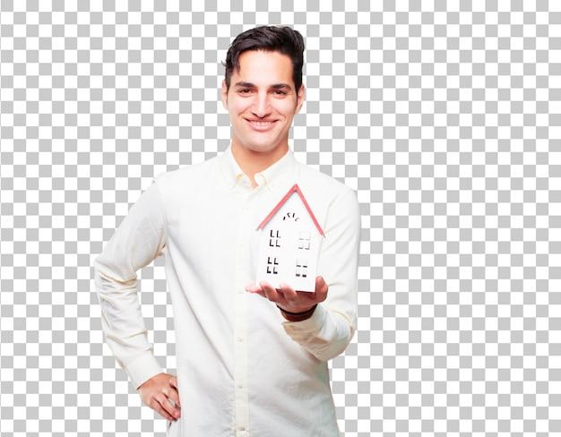 Jonge knappe gebruinde man met een huis-model