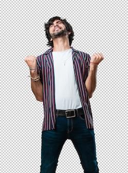 Jonge knappe man erg blij en opgewonden, armen omhoog, een overwinning of een succes vieren, de loterij winnen