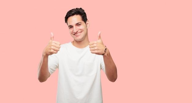 Jonge knappe man met een tevreden, trots en gelukkig uiterlijk met duimen omhoog