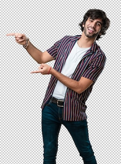 Jonge knappe man wijst naar de kant, glimlachend verrast presenteren iets, natuurlijk en casual
