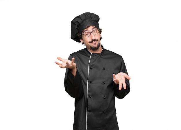 Jonge man chef met een vragende en verwarde blik, twijfelt tussen verschillende keuzes