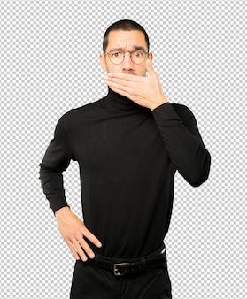 Jonge man die zijn mond bedekt met zijn handen