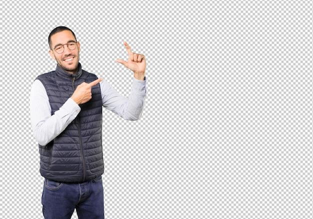 Jonge man doet een gebaar van kleine omvang met zijn hand