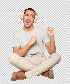 Jonge man in zittende positie met een feestelijk gebaar