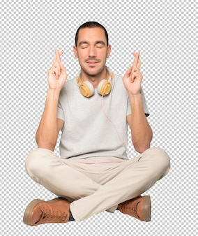 Jonge man in zittende positie met een gebaar met gekruiste vingers