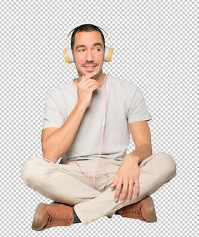 Jonge man in zittende positie met een twijfelgebaar