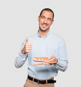 Jonge man met stokjes om sushi te eten