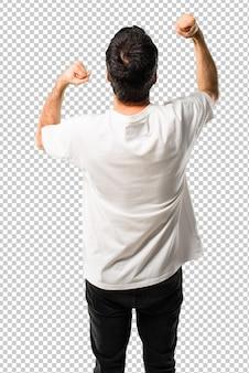 Jonge man met wit overhemd een overwinning te vieren en verrast om succesvol te zijn