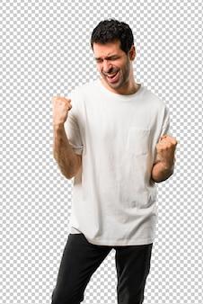 Jonge man met wit overhemd een overwinning vieren en blij dat hij een prijs heeft gewonnen