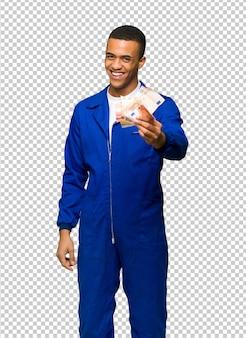 Jonge man van de afro amerikaanse arbeider die heel wat geld neemt