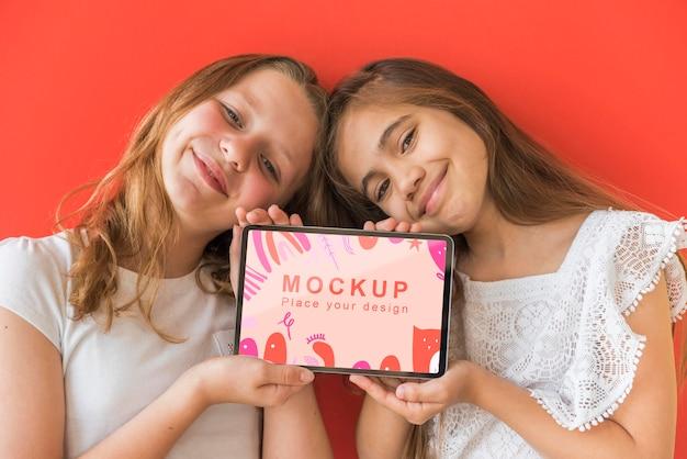 Jonge meisjes die telefoon met model houden
