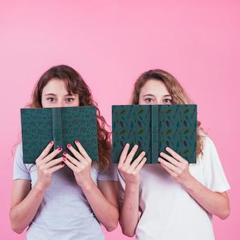 Jonge meisjes houden boekomslag mockup
