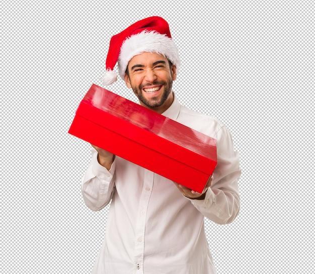 Jonge mens die een hoed van de kerstman op kerstdag draagt