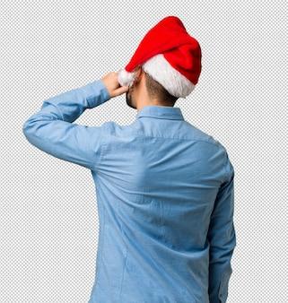 Jonge mens die santahoed draagt van achter het denken over iets
