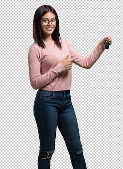 Jonge mooie vrouw blij en glimlachend, met de sleutels van de auto, zelfverzekerd, biedt ze aan om uw nieuwe auto te starten