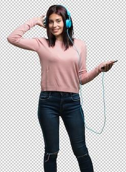Jonge mooie vrouw blij en leuk, luisterend naar muziek, moderne koptelefoons, blij het geluid en het ritme voelen