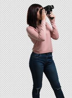 Jonge mooie vrouw opgewonden en vermaakt, kijkend door een filmcamera, op zoek naar een interessant schot, opname van een film, uitvoerend producent