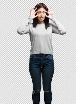 Jonge mooie vrouw verrast en geschokt, kijkend met grote ogen, opgewonden door een aanbieding of door een nieuwe baan, win concept