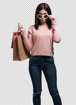 Jonge mooie vrouw vrolijk en glimlachend, erg opgewonden met boodschappentassen, klaar om te gaan winkelen en op zoek te gaan naar nieuwe aanbiedingen