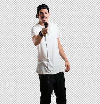 Jonge rapper man blij en gemotiveerd, zingt een lied met een microfoon, presenteert een evenement of heeft een feest, geniet van het moment