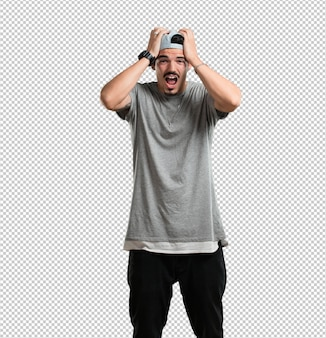 Jonge rapper man gefrustreerd en wanhopig, boos en verdrietig met de handen op het hoofd