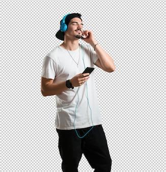 Jonge rapper man ontspannen en geconcentreerd, luisterend naar muziek met zijn mobiele telefoon, voel het ritme en ontdek nieuwe artiesten, ogen dicht