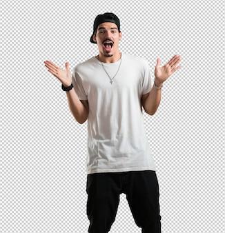 Jonge rapper man schreeuwt blij, verrast door een aanbieding of promotie, gapend, springend en trots