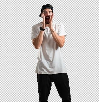 Jonge rapper man schreeuwt blij, verrast door een aanbod of een promotie, gapend, springend en trots