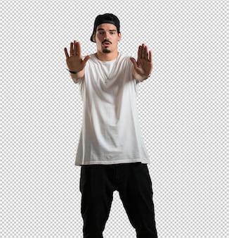 Jonge rapper man serieus en vastberaden, hand in front, stop gebaar, ontkennen concept