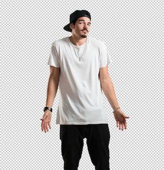 Jonge rapper man twijfelt en haalt zijn schouders op, concept van besluiteloosheid en onzekerheid, onzeker over iets