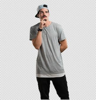Jonge rapper man twijfelt en verward, denkt aan een idee of maakt zich ergens zorgen over