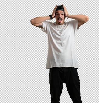 Jonge rapper man verrast en geschokt, kijkend met grote ogen, opgewonden door een aanbieding of door een nieuwe baan, win concept