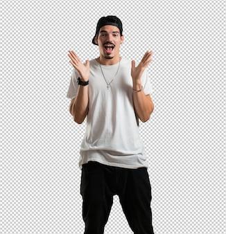 Jonge rapper man verrast en geschokt, kijkt met grote ogen, opgewonden door een aanbod of door een nieuwe baan, win concept