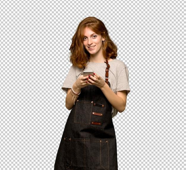 Jonge redhead vrouw die met schort een bericht met mobiel verzendt