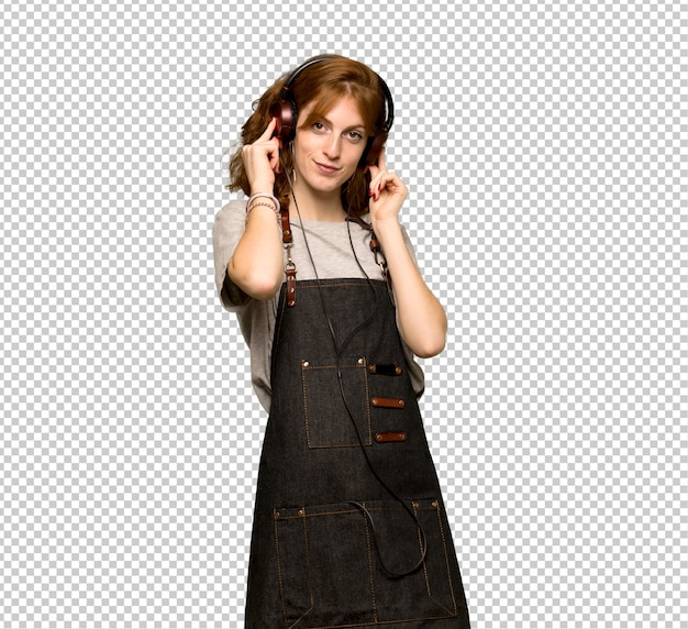 Jonge roodharigevrouw met schort die aan muziek met hoofdtelefoons luisteren