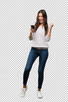 Jonge spaanse donkerbruine vrouw met telefoon in overwinningspositie