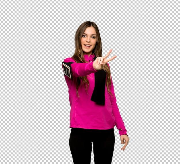 Jonge sportvrouw die en overwinningsteken glimlacht toont